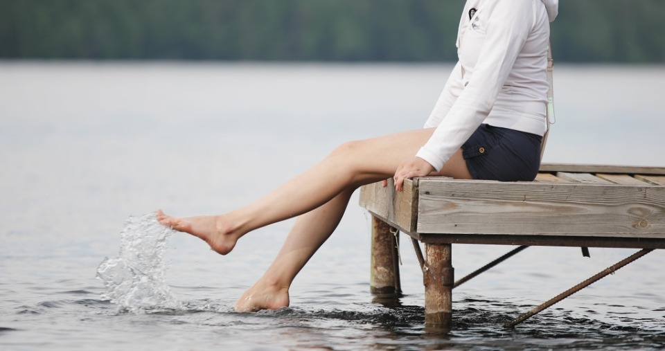 Woman relaxes by the lake - Home